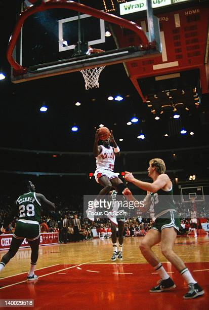 Michael Jordan of the Chicago Bulls goes in for a layup over Larry Bird of the Boston Celtics during an NBA basketball game circa 1985 at the Chicago...