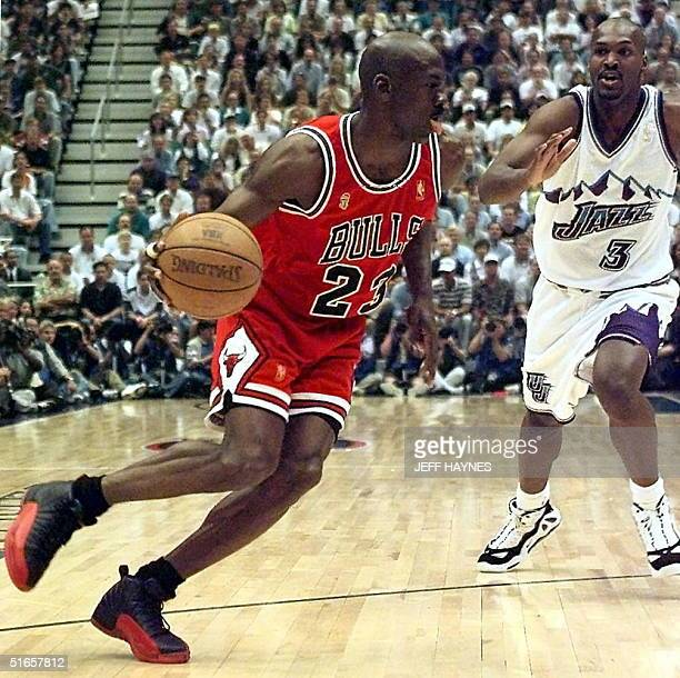 Michael Jordan of the Chicago Bulls goes to the basket past Bryon Russell of the Utah Jazz 11 June during game five of the 1997 NBA Finals at the...