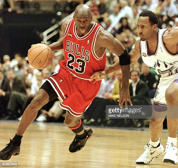 Michael Jordan of the Chicago Bulls goes to the basket past Shandon Anderson of the Utah Jazz 14 June during game six of the NBA Finals at the Delta...