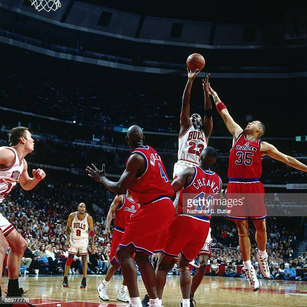 Michael Jordan of the Chicago Bulls goes up for a shot against Chris Webber Calbert Cheaney and Tracy Murray of the Washington Bullets in Game Two of...