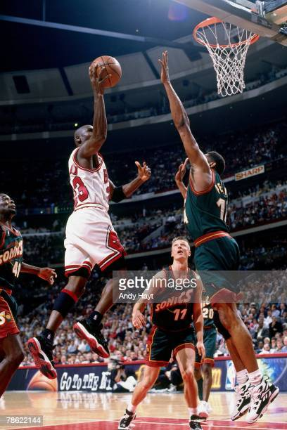 Michael Jordan of the Chicago Bulls goes up for a shot against Sam Perkins of the Seattle SuperSonics during Game One of the NBA Finals at the United...