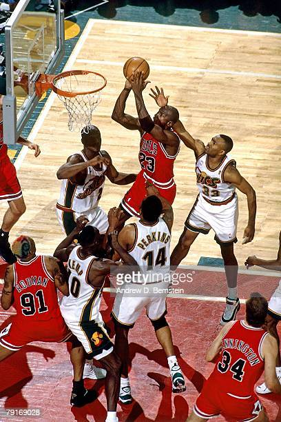 Michael Jordan of the Chicago Bulls goes up for a shot against Sam Perkins and Shawn Kemp of the Seattle SuperSonics in Game Three of the 1996 NBA...