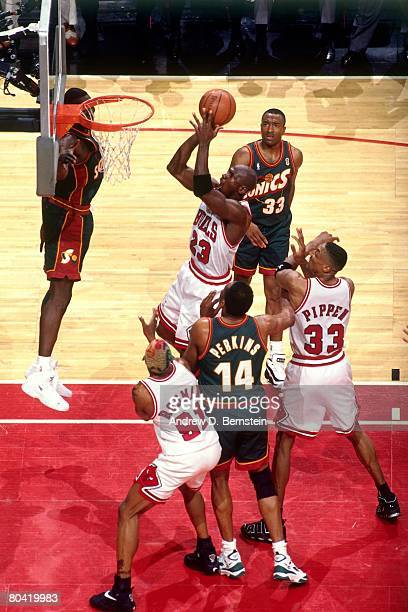 Michael Jordan of the Chicago Bulls goes up for a shot against Sam Perkins of the Seattle SuperSonics during Game Six of the 1996 NBA Finals at the...