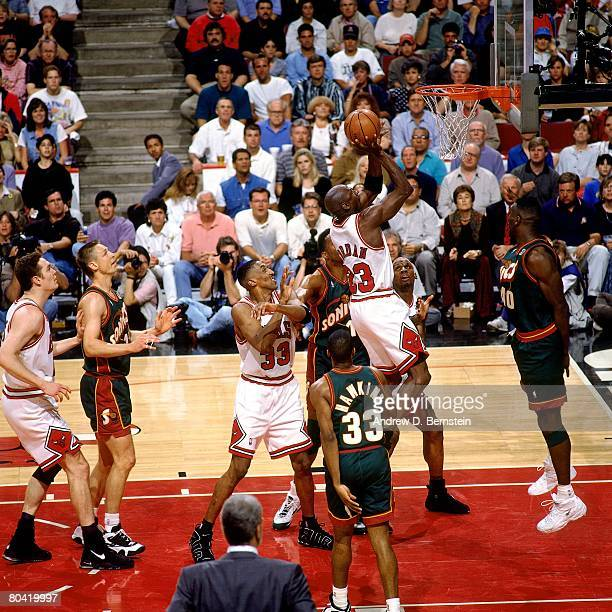 Michael Jordan of the Chicago Bulls goes up for a shot against Shawn Kemp of the Seattle SuperSonics in Game Six of the 1996 NBA Finals at the United...