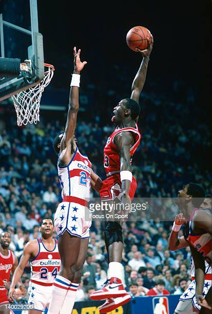 Michael Jordan of the Chicago Bulls goes up to jam on Charles Jones of the Washington Bullets during an NBA basketball game circa 1985 at the Capital...