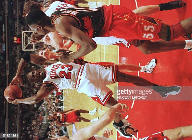 Michael Jordan of the Chicago Bulls grabs a rebound as Dikembe Mutombo of the Atlanta Hawks looks on during the first half of game two of their...