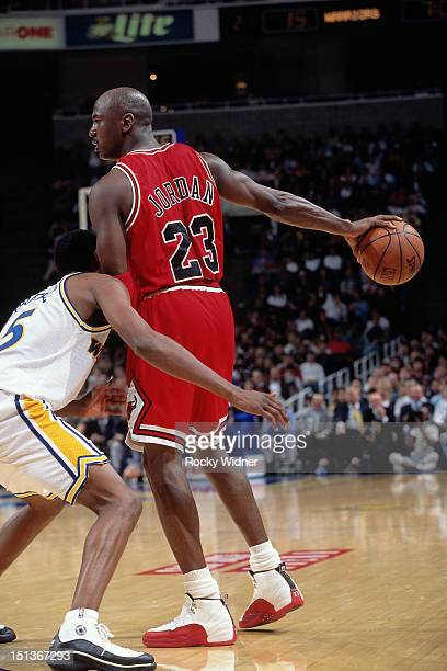 Michael Jordan of the Chicago Bulls handles the ball against Latrell Sprewell of the Golden State Warriors on January 31 1997 at San Jose Arena in...