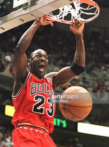 Michael Jordan of the Chicago Bulls hang son the rim after a dunk 05 June against the Utah Jazz in game two of the NBA Finals at the Delta Center in...