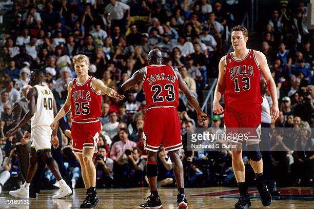 Michael Jordan of the Chicago Bulls high fives teammates Steve Kerr and Luc Longley against the Seattle SuperSonics in Game Three of the 1996 NBA...