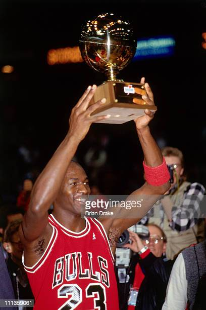 Michael Jordan of the Chicago Bulls hoists the trophy after winning the 1988 NBA Slam Dunk Contest on February 6 1988 at Chicago Stadium in Chicago...