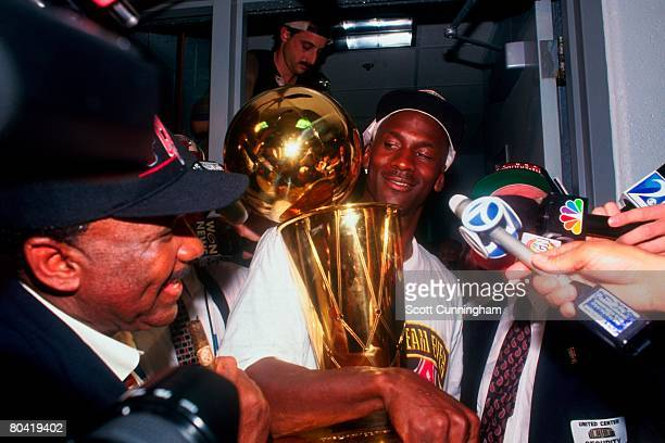 Michael Jordan of the Chicago Bulls hold the Larry O'Brien Championship Trophy after defeating the Seattle Super Sonics in Game Six of the 1996 NBA...