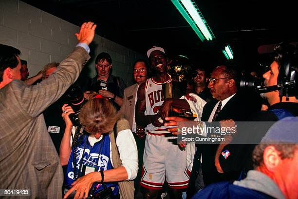 Michael Jordan of the Chicago Bulls hold the Larry O'Brien Championship Trophy after defeating the Seattle SuperSonics in Game Six of the 1996 NBA...