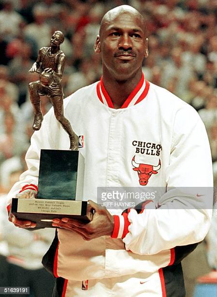 Michael Jordan of the Chicago Bulls holds his fifth Maurice Podoloff Most Valuable Player Trophy for the 199798 season giving to him 19 May before...