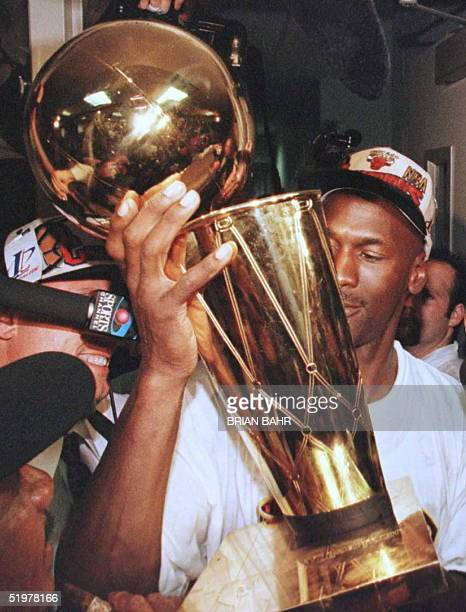 Michael Jordan of the Chicago Bulls holds the Larry O'Brian trophy outside the Bulls locker room after game six of the NBA Finals at the United...