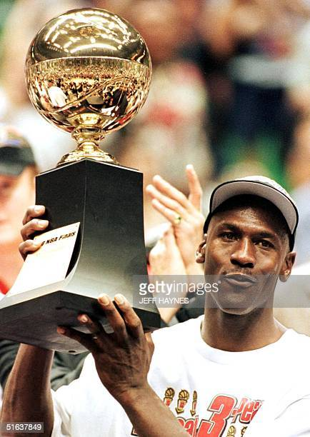 Michael Jordan of the Chicago Bulls holds the Most Valuable Player trophy 14 June after the Bulls won game six of the NBA Finals with the Utah Jazz...