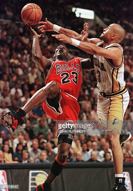 Michael Jordan of the Chicago Bulls is fouled by Mark Jackson of the Indiana Pacers 25 May during the second half of game four of their NBA Eastern...