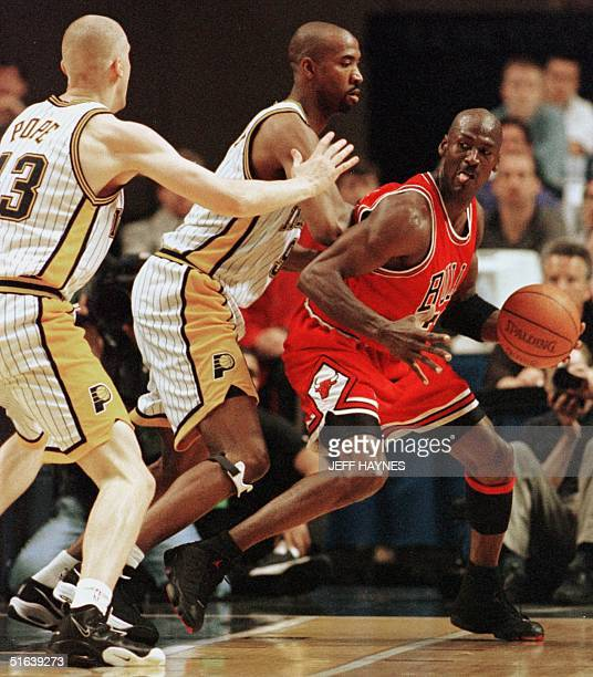 Michael Jordan of the Chicago Bulls is guarded by Derrick McKey and Mark Pope of the Indiana Pacers 23 May during the first half of game three of...