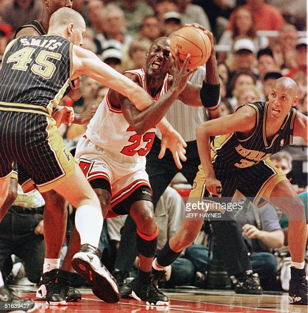 Michael Jordan of the Chicago Bulls is guarded by Rik Smits and Reggie Miller of the Indiana Pacers 31 May during the first half of game seven of...
