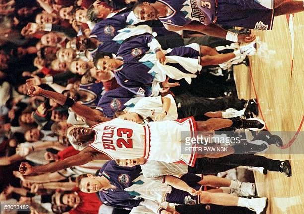 Michael Jordan of the Chicago Bulls jumps in the air as Karl Malone of the Utah Jazz walks off the court 13 June after game six of the 1997 NBA...