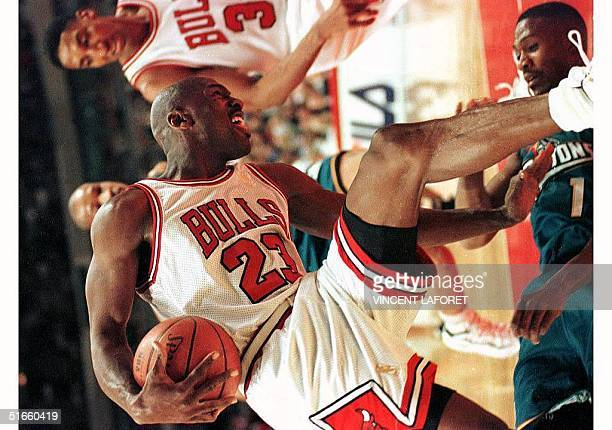 Michael Jordan of the Chicago Bulls jumps over Detroit Pistons guard Lindsey Hunter, below, after they collided in the first quarter of their 22...