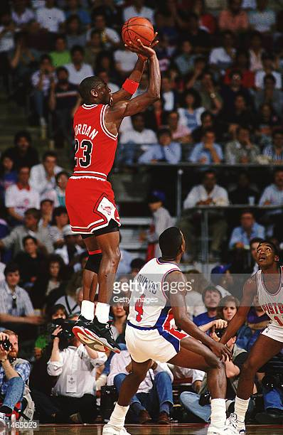 Michael Jordan of the Chicago Bulls jumps to shoot the ball during a game against the Detroit Pistons NOTE TO USER It is expressly understood that...