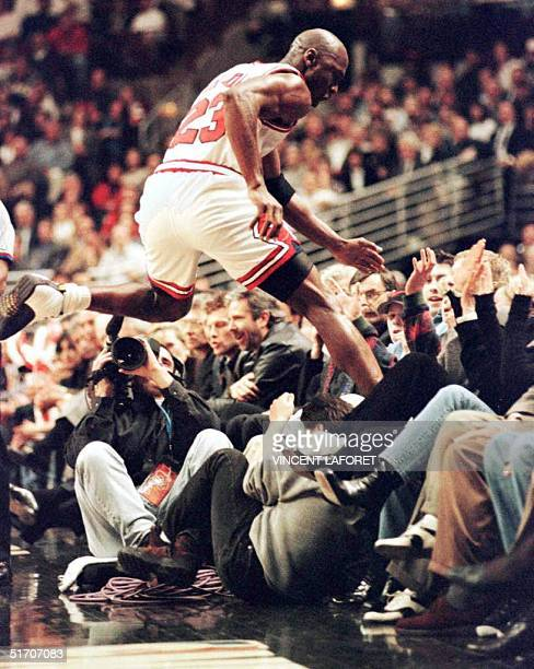 Michael Jordan, of the Chicago Bulls, leaps into the crowd chasing a lose ball 25 March 1997 during the first half of his team's game against the...