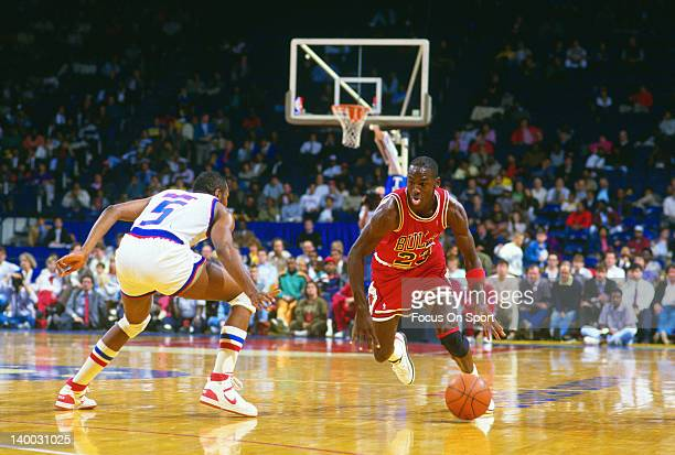 Michael Jordan of the Chicago Bulls looks to dribble pass Darrell Walker of the Washington Bullets during an NBA basketball game circa 1988 at the...