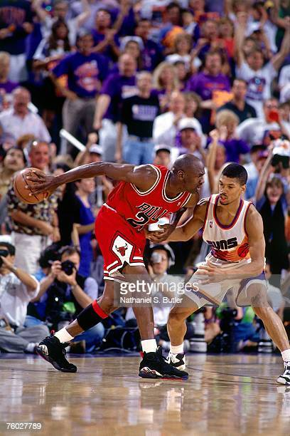 Michael Jordan of the Chicago Bulls looks to drive to the basket against Kevin Johnson of the Phoenix Suns in Game Six of the 1993 NBA Finals on June...