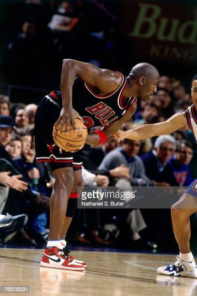 Michael Jordan of the Chicago Bulls looks to make a move while wearing his original Nike sneakers against the New York Knicks during his final game...