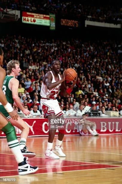 Michael Jordan of the Chicago Bulls looks to make a pass during the 1980 NBA game against the Boston Celtics at Chicago Stadium in Chicago Illinois...
