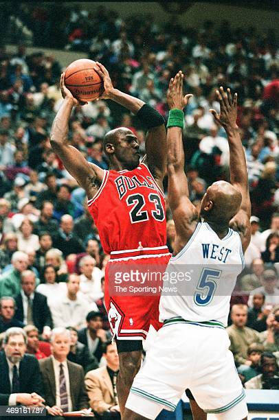 Michael Jordan of the Chicago Bulls looks to move the ball against Doug West of the Minnesota Timberwolves during the game on February 16, 1996 at...