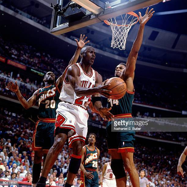 Michael Jordan of the Chicago Bulls looks to pass against Sam Perkins of the Seattle SuperSonics during Game Six of the 1996 NBA Finals at the United...