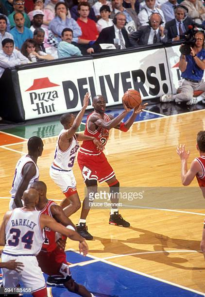 Michael Jordan of the Chicago Bulls looks to pass as he is defended by Hersey Hawkins of the Philadelphia 76ers duing a game in the 1991 Eastern...