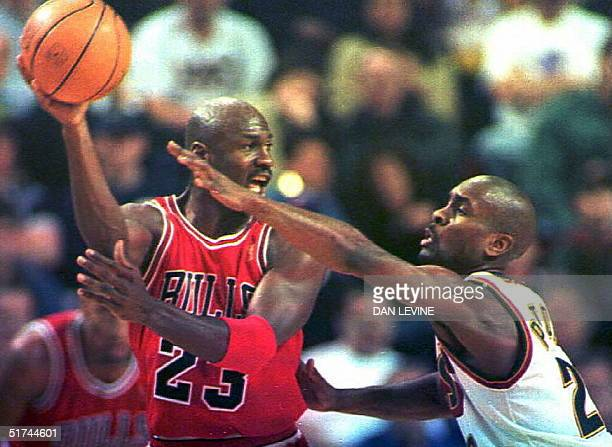 Michael Jordan of the Chicago Bulls looks to pass the ball as Seattle SuperSonics defender Gary Payton guards him during first quarter action in...