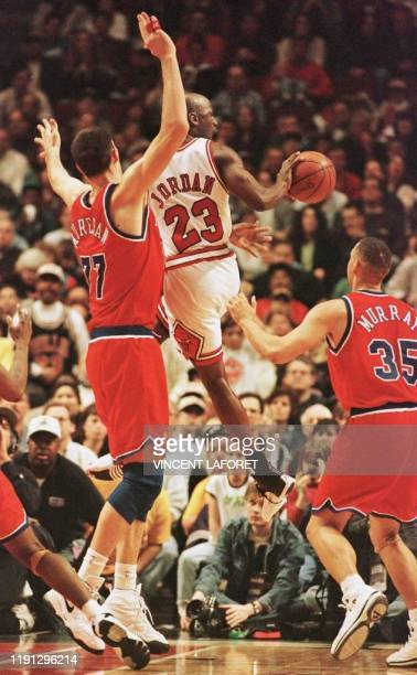 Michael Jordan of the Chicago Bulls makes a pass between Gheorghe Muresan and Tracy Murray of the Washington Bullets 27 April 1997 during the first...