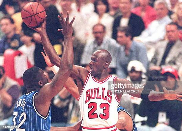 Michael Jordan of the Chicago Bulls passes the ball off under pressure from Orlando Magic center Shaquille O'Neal in the first quarter of their NBA...