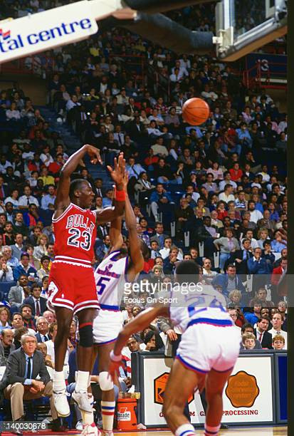 Michael Jordan of the Chicago Bulls passes the ball over Darrell Walker of the Washington Bullets during an NBA basketball game circa 1987 at the...