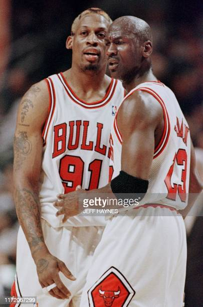 Michael Jordan of the Chicago Bulls pulls teammate Dennis Rodman away after Rodman was called for a technical foul 27 May during the first half of...