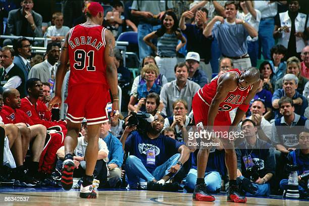 Michael Jordan of the Chicago Bulls rests as teammate Dennis Rodman walks by during Game Five of the 1997 NBA Finals played against the Utah Jazz on...