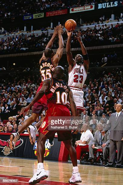 Michael Jordan of the Chicago Bulls shoots a jump shot against Darrin Hancock and Mookie Blaylock of the Atlanta Hawks in Game One of the Eastern...