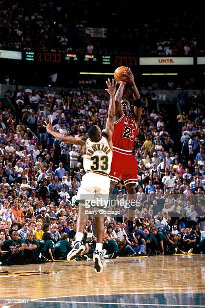 Michael Jordan of the Chicago Bulls shoots a jump shot over Hersey Hawkins of the Seattle SuperSonics in Game Five of the 1996 NBA Finals at Key...