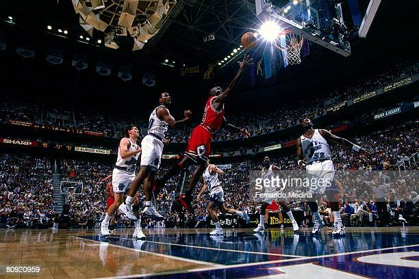Michael Jordan of the Chicago Bulls shoots a layup against Karl Malone of the Utah Jazz in Game One of the 1998 NBA Finals at the Delta Center on...