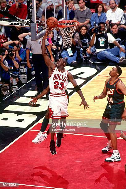 Michael Jordan of the Chicago Bulls shoots a layup against Sam Perkins of the Seattle SuperSonics during Game Six of the 1996 NBA Finals at the...