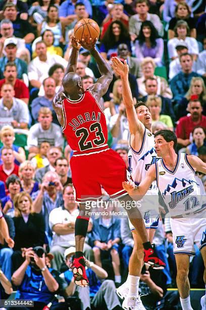 Michael Jordan of the Chicago Bulls shoots against Jeff Hornacek and John Stockton of the Utah Jazz during Game one of the 1998 NBA Finals on June 3...