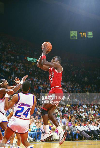 Michael Jordan of the Chicago Bulls shoots over Jeff Malone and Moses Malones of the Washington Bullets during an NBA basketball game circa 1987 at...