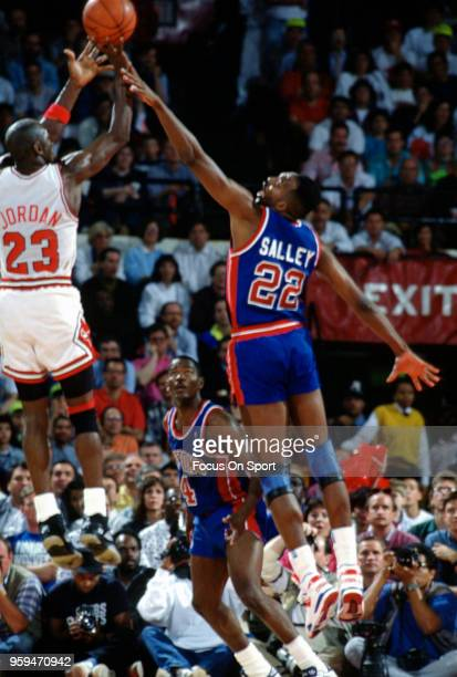 Michael Jordan of the Chicago Bulls shoots over John Salley of the Detroit Pistons during an NBA basketball game circa 1990 at the Chicago Stadium in...