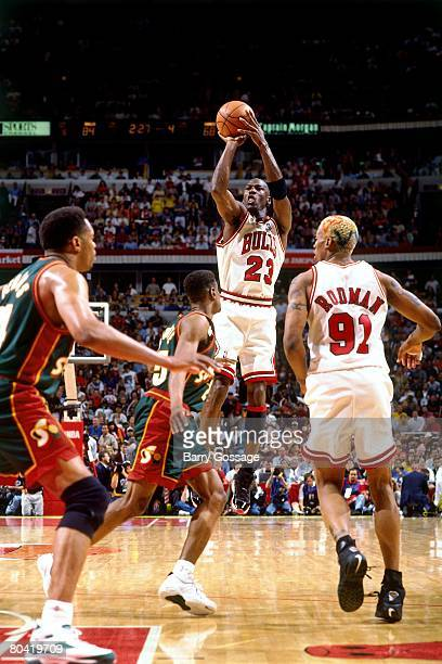 Michael Jordan of the Chicago Bulls shotos a jump shot against Sam Perkins of the Seattle SuperSonics during Game Six of the 1996 NBA Finals at the...