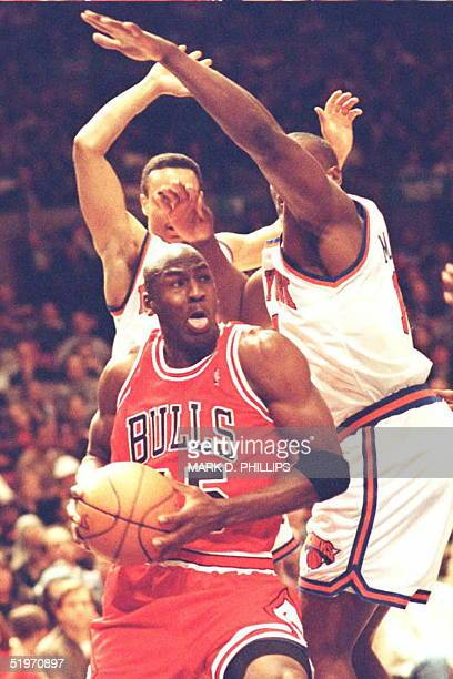Michael Jordan of the Chicago Bulls slips underneath Anthony Mason and John Starks of the New York Knicks during first half action on March 28 1995...