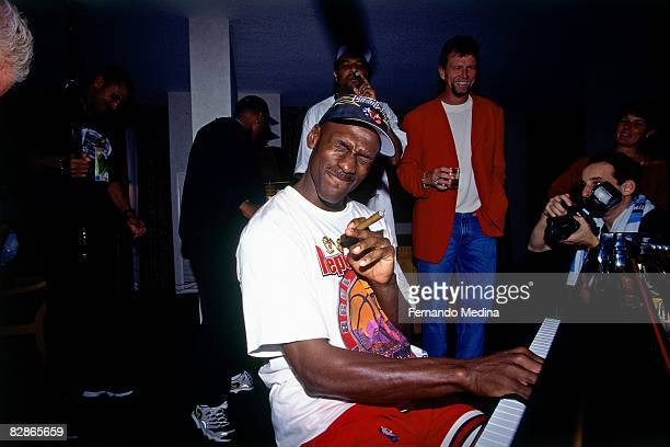 Michael Jordan of the Chicago Bulls smokes a cigar while playing the piano following Game Six of the 1998 NBA Finals played June 14, 1998 at the...