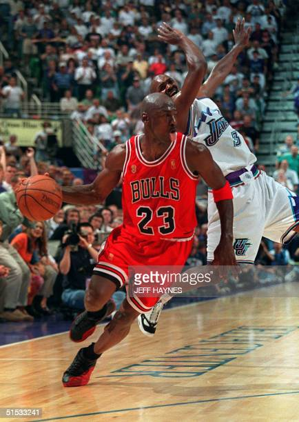 Michael Jordan of the Chicago Bulls sticks out his tongue as he goes past Bryon Russell of the Utah Jazz 11 June 1997 during game five of the 1997...